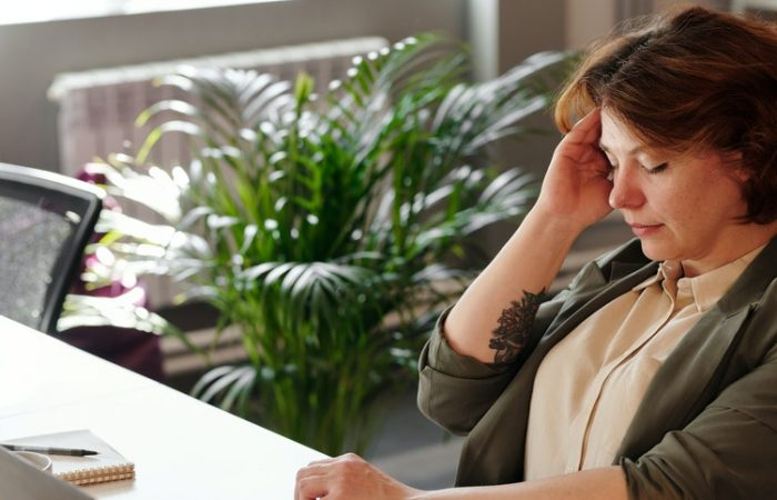 woman holding her head while working from home