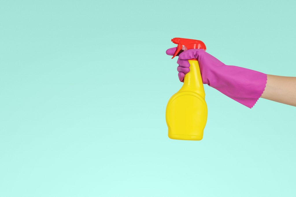 A woman's gloved hand holding a spray bottle in order to clean the house
